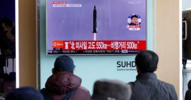 People listen to news about North Korea missile test