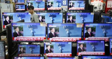 A Korean sales assistant watches TV after North Korea missile test