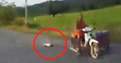 Monk dragging dog along road