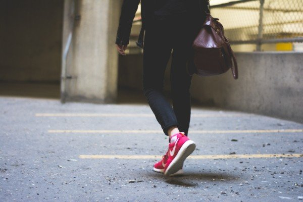 person-walking-city-street-shoes-red-nike-bag
